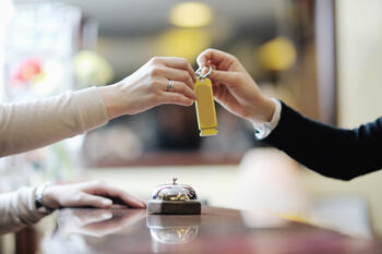 hotel-worker-hands-guest-key-great-hospitality