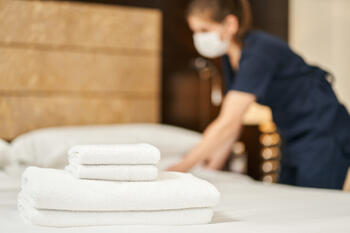 hotel-housekeeper-changing-bed-sheets-during-pandemic